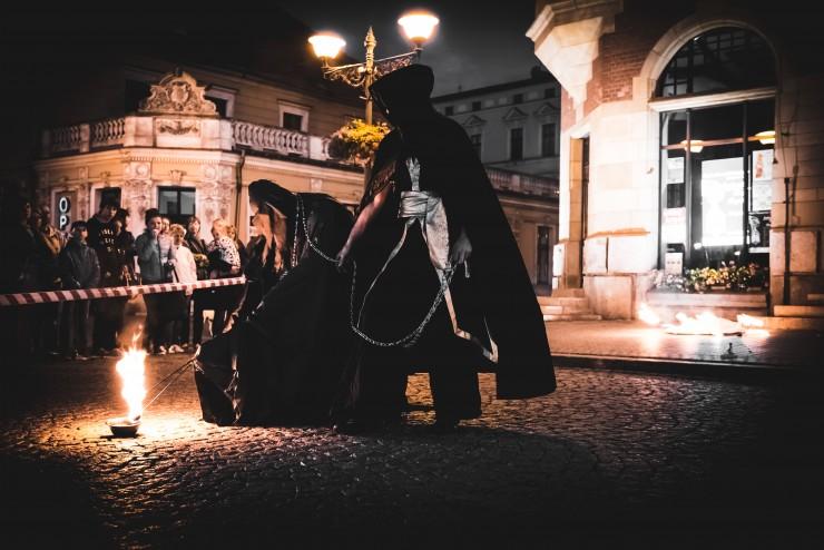 mężczyzna w pelerynie oraz potwór wykonują pokaz teatru ognia podczas halloween
