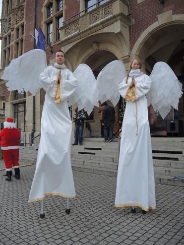 dwóch tancerzy w strojach aniołków na szczudłach