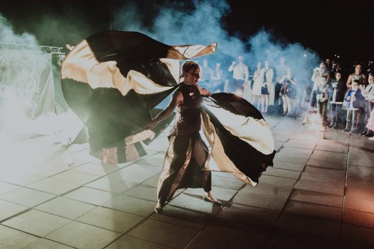 widownia obserwująca oświetloną artystkę wykonującą taniec ze skrzydłami isis