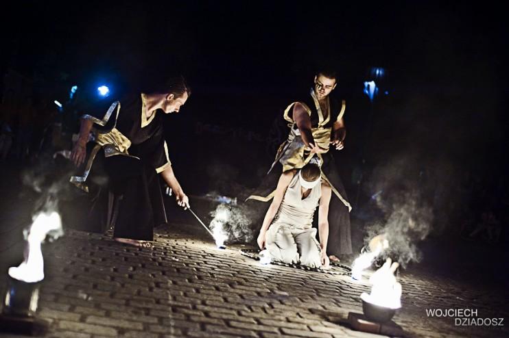 leżąca artystka w płonącym hulahopie oraz dwóch tancerzy ognia zapalających płonące rekwizyty