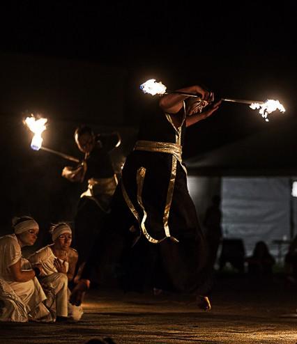 dwóch artystów z płonącymi kijami podczas skoku