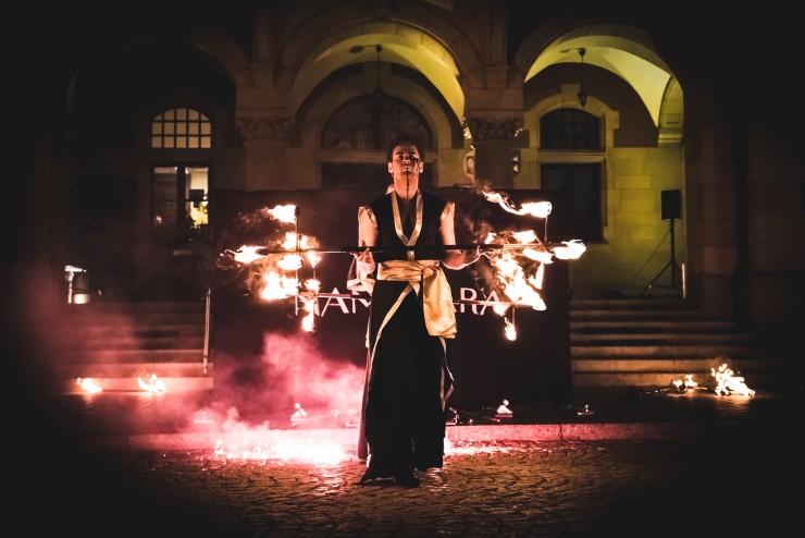 mężczyzna w złoto czarnym stroju trzymający płonący kij