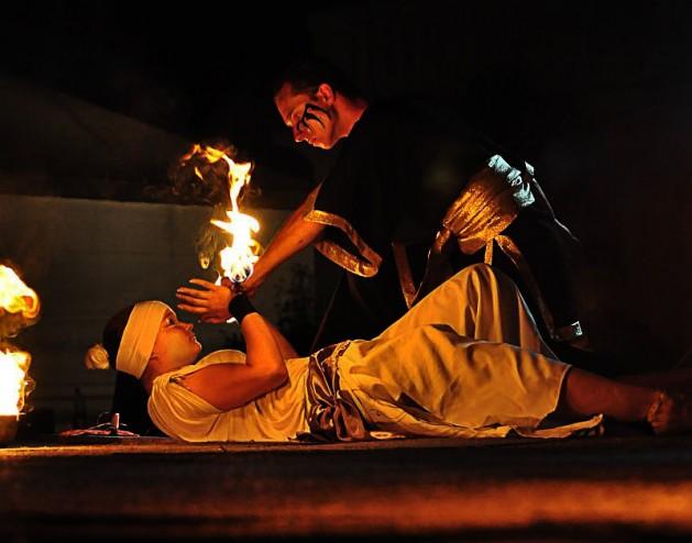 mężczyzna pochylający się nad leżącą artystką z płonącym rekwizytem