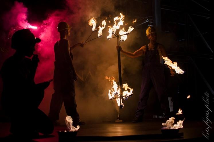 artyści w dymie wykonujący scenę z teatru ognia o tematyce industrialnej