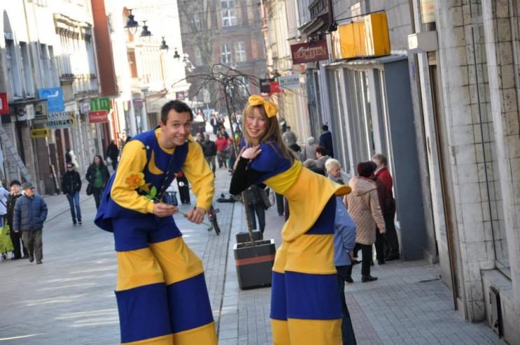 dwóch artystów w strojach niebiesko żółtych na ulicy