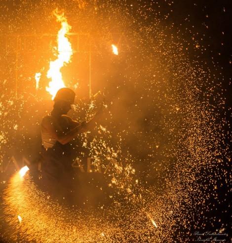tancerz ognia w stroju robotnika w kasku podczas ognistego wybuchu