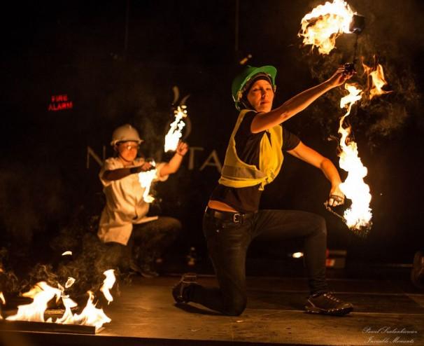dwie artystki z płonącymi poi w kaskach