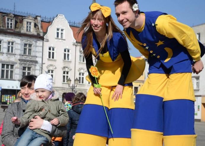 dwoje tancerzy na szczudłach w strojach niebiesko żółtych
