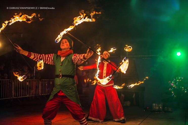 dwóch artystów w strojach elfa i mikołaja podczas ognistego pokazu