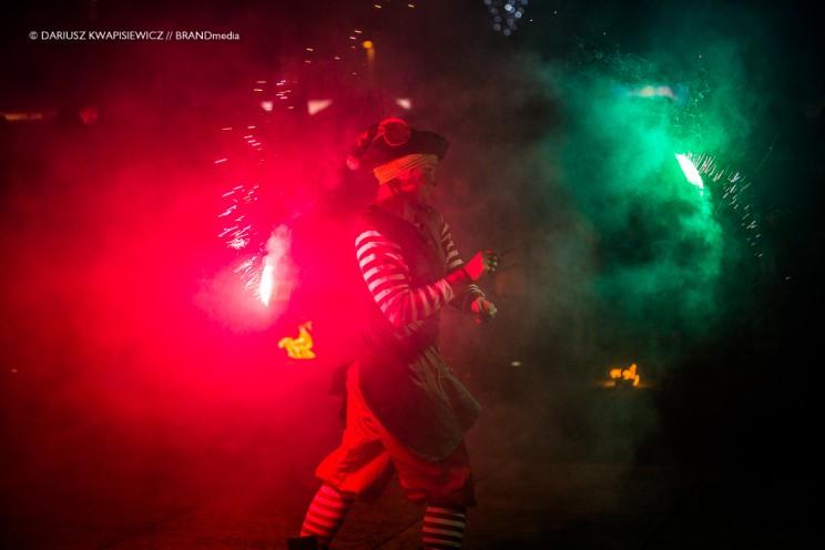 artysta w dymie z rekwizytami świecącymi w kolorze czerwonym i zielonym