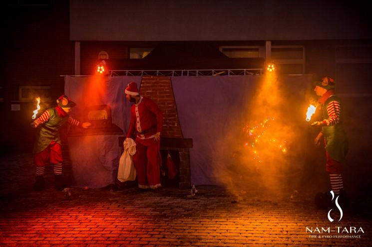 trzech artystów wykonujących scenę z mikołajkowego pokazu ognia