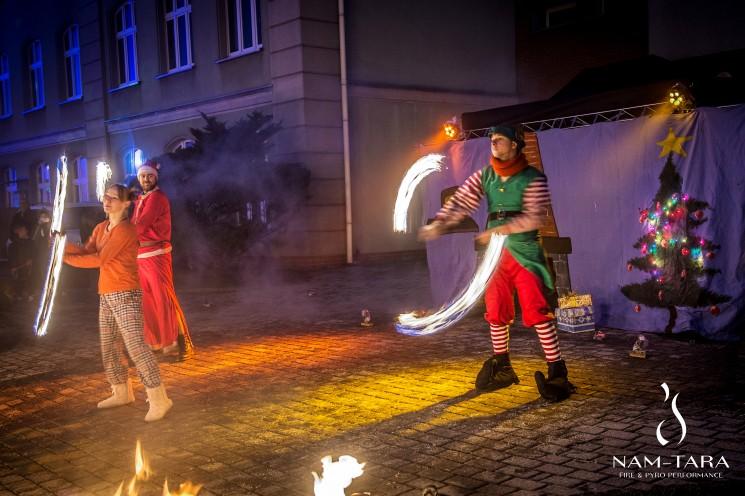 trzech artystów z płonącymi rekwizytami w strojach elfa, dziewczynki oraz mikołaja