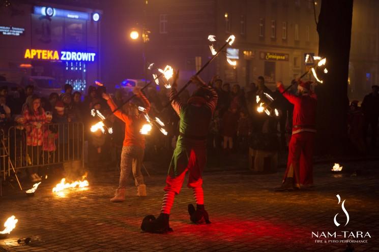 trzech tancerzy ognia wykonujących świąteczny pokaz teatru ognia na jarmarku świątecznym
