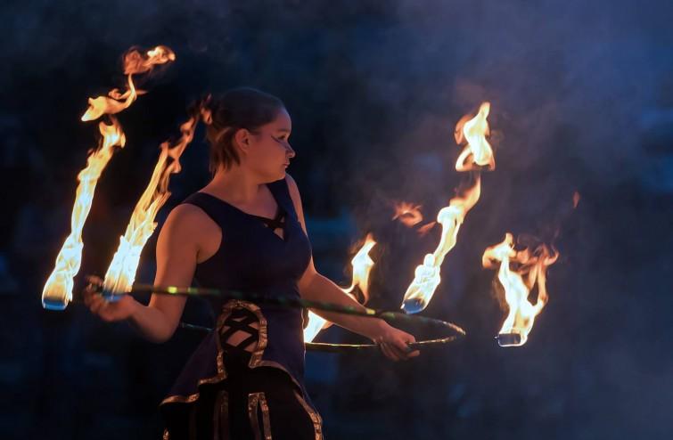 artystka w niebieskim stroju z płonącym hulahopem