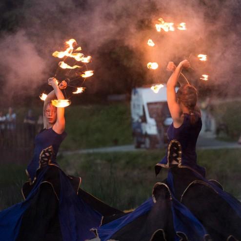 dwie artystki z płonącymi wachlarzami w niebieskim spódnicach