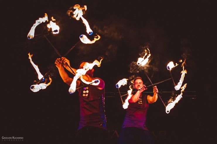 dwóch tancerzy ognia z płonącymi rekwizytami