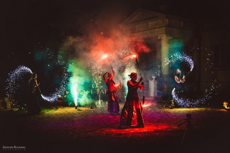 czterech tancerzy ognia wykonujących ognisty taniec w różnych kolorach