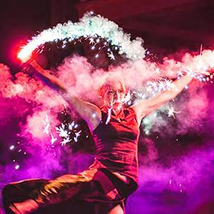 tancerka ognia wykonująca pokaz ognia na weselu z iskrzącymi racami w rękach w kolorze fioletowym