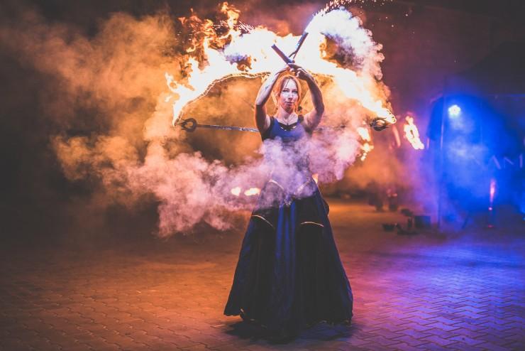 tancerz ognia podczas spektaklu teatru ognia w niebieskiej spódnicy oraz płonącymi pałkami w rękach