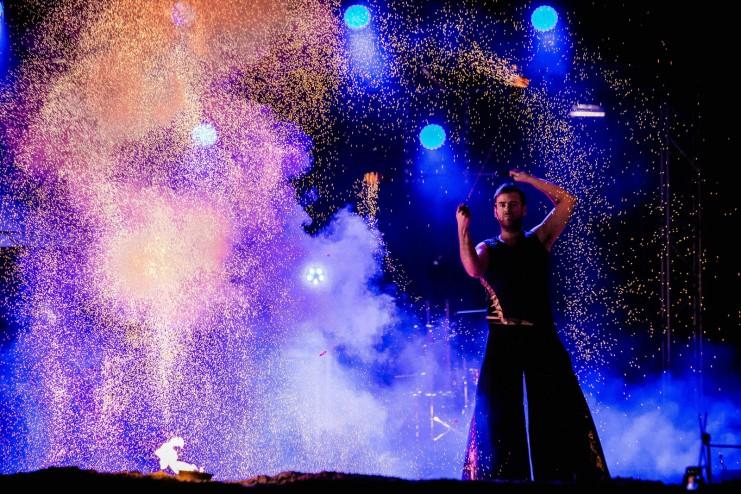 tancerz ognia w chmurze iskier podczas pokazu ognia