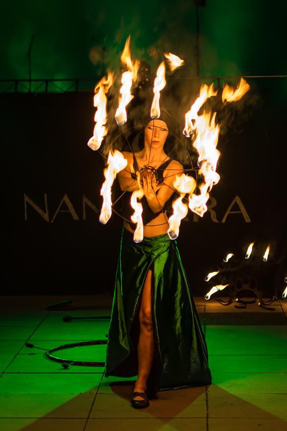 kobieta z płonącymi wachlarzami w zielonej spódnicy