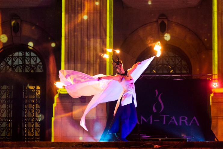 tancerka ognia wykonująca ognisty taniec w płonącej koronie oraz białych skrzydłach