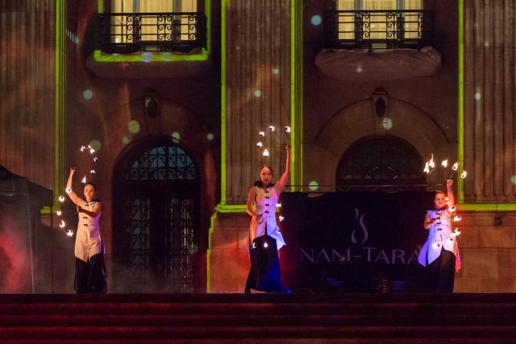 trzy tancerki w białych strojach podczas układu z płonącymi wachlarzami