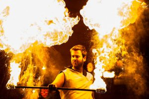 mężczyzna wbiałym stroju wykonujący ogniste ewolucje podczas pokazu teatru ognia