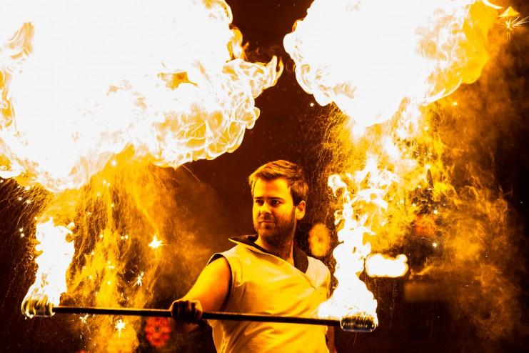 mężczyzna w białym stroju wykonujący ogniste ewolucje podczas pokazu teatru ognia