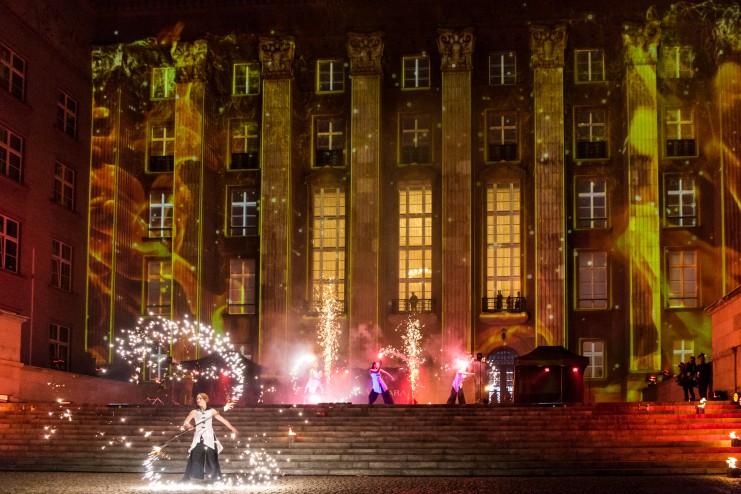 tancerze ognia wykonujący pokaz teatralny w kolorach białych na tle urzędu wojewódzkiego w katowicach