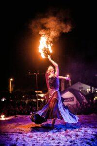 tancerka ognia wniebieskiej spódnicy tańczy zpłonącymi wachlarzami
