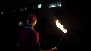 tancerz ognia wstroju mikołaja zpłonącą pochodnią wręku patrzy się nabalkony woddali, gdzie stoi widownia