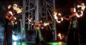 trzech tancerzy ognia nascenie wczarno-zielonych strojach zpłonącymi rekwizytami wrękach